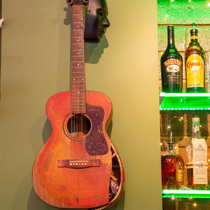 Restaurant decorations, guitar on the wall, bottles of hard drink on the shelves