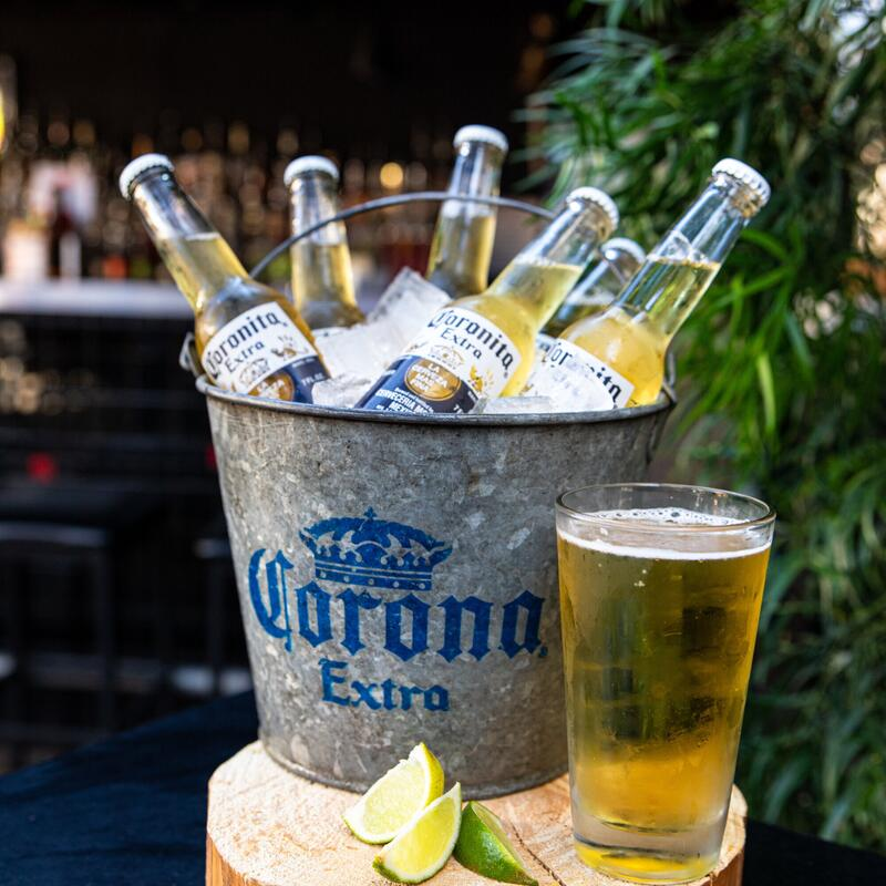 Corona beers on ice and a glass of beer with limes