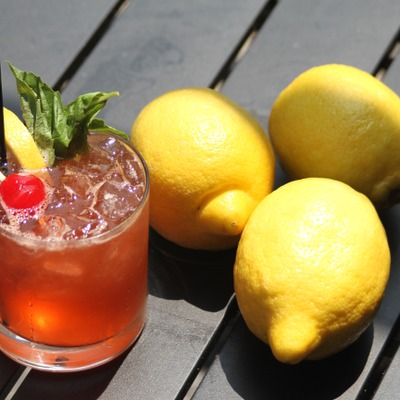 Deep orange cocktail with decorations and three lemons
