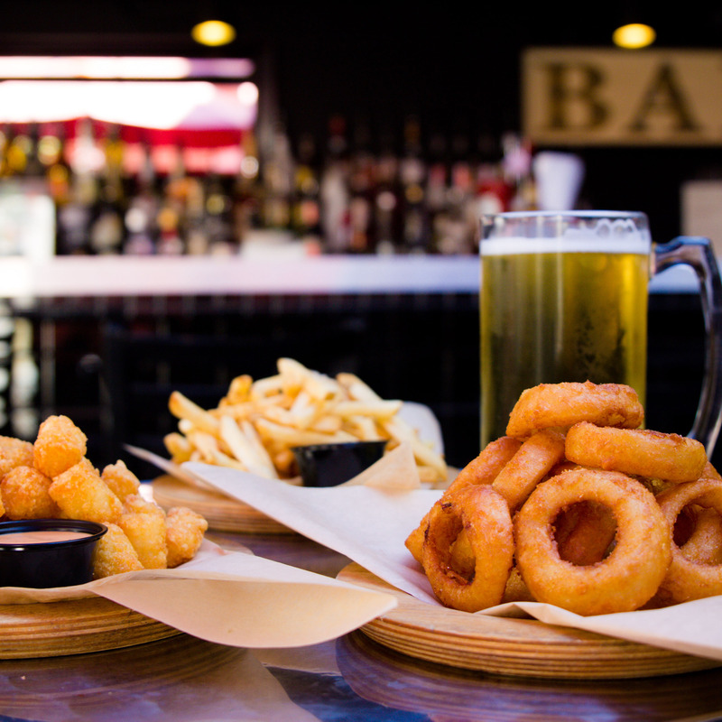 Onion rings, fries and nuggets with dip and a stein of draft beer