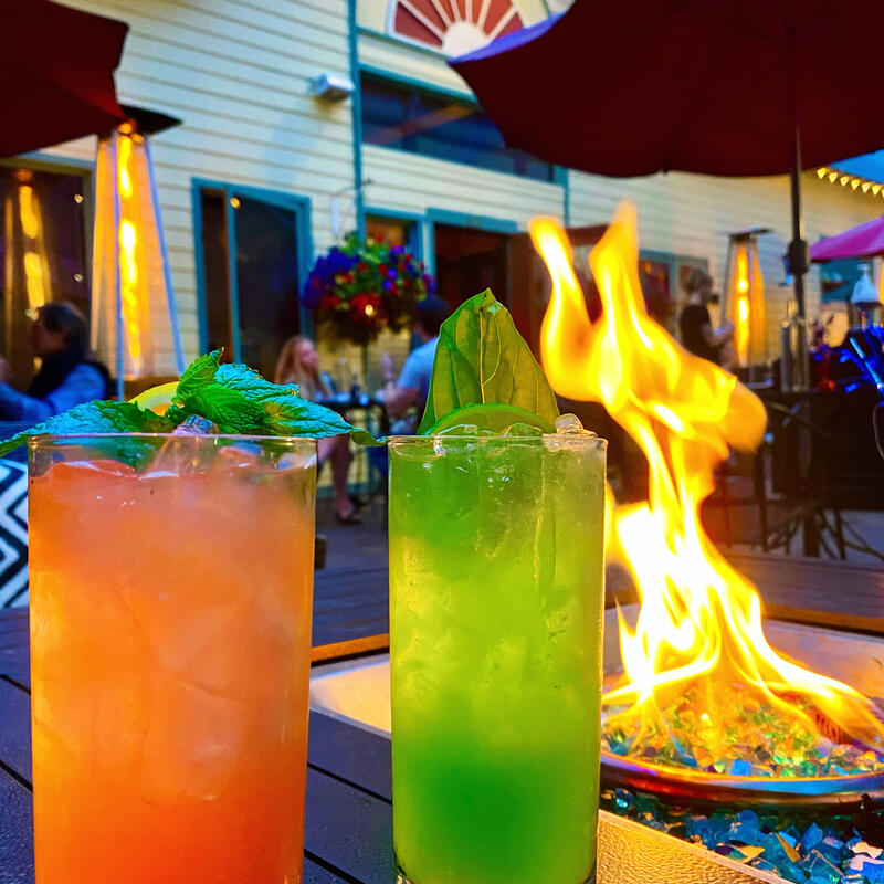 Orange and green cocktails in front of a fire
