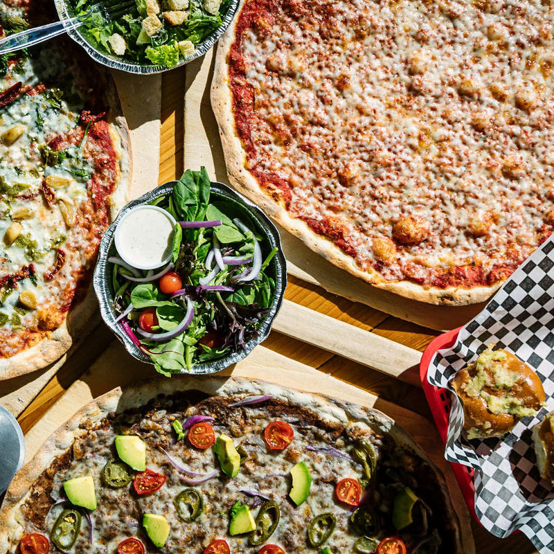 Various dishes on the table, salads, pizzas, top view