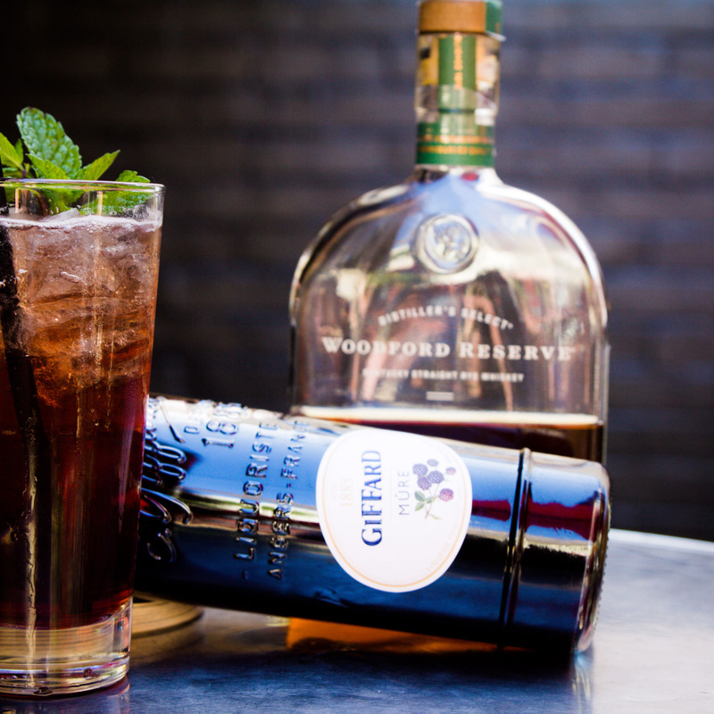 A dark cocktail and bottles of Giffard and Woodford Reserve