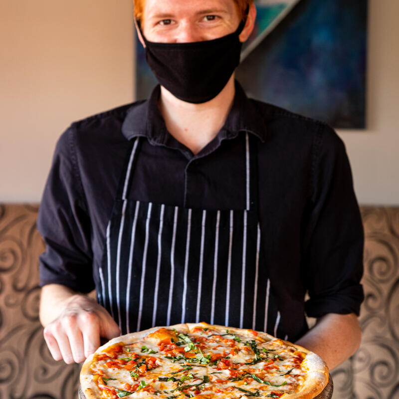 Staff member with a mask holding a pizza