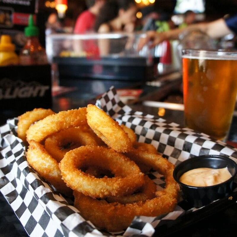Onion rings with dip on the side. glass of beer in the back