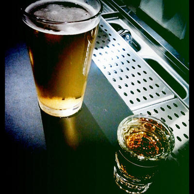 A glass of beer and a shot glass