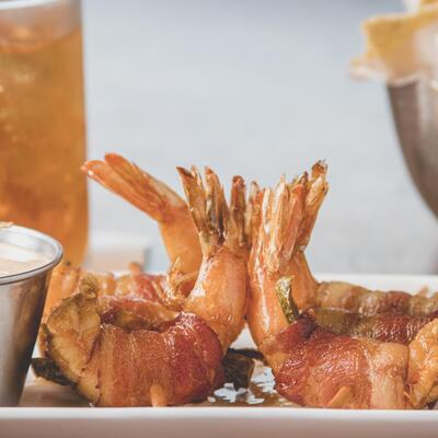 Shrimps with bacon, white dip on the side