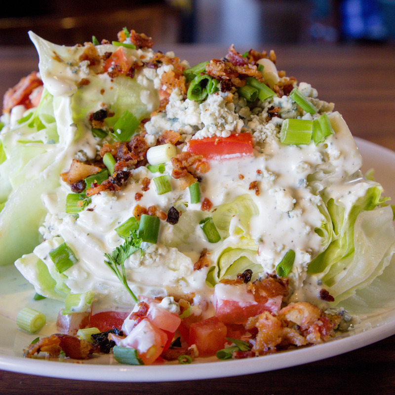 Wedge salad: Iceberg lettuce, bleu cheese crumbles, crispy bacon bits, tomato, green onion, bleu cheese dressing