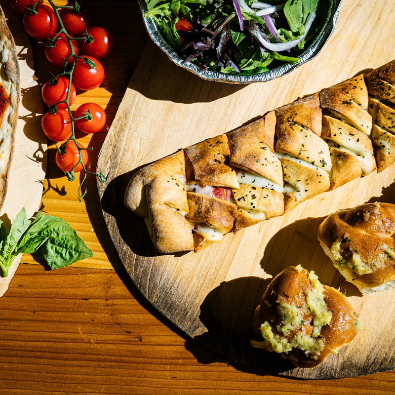 Filled pastries of various shapes, salad and cherry tomatoes