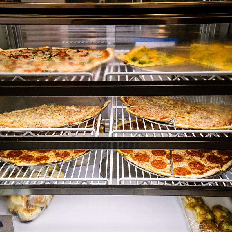 Various pizzas in a display case