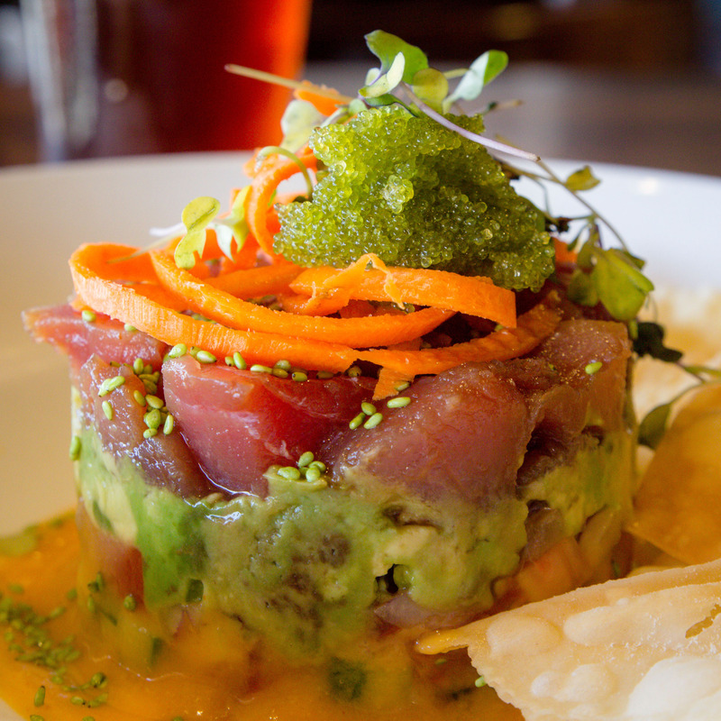 Ahi Stack. Fresh tuna, smashed avocado,cucumber,tomato,onion,mango habenero puree and fried wonton chips