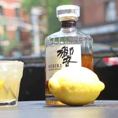 Yellow cocktail, a lemon and a bottle of suntory whiskey