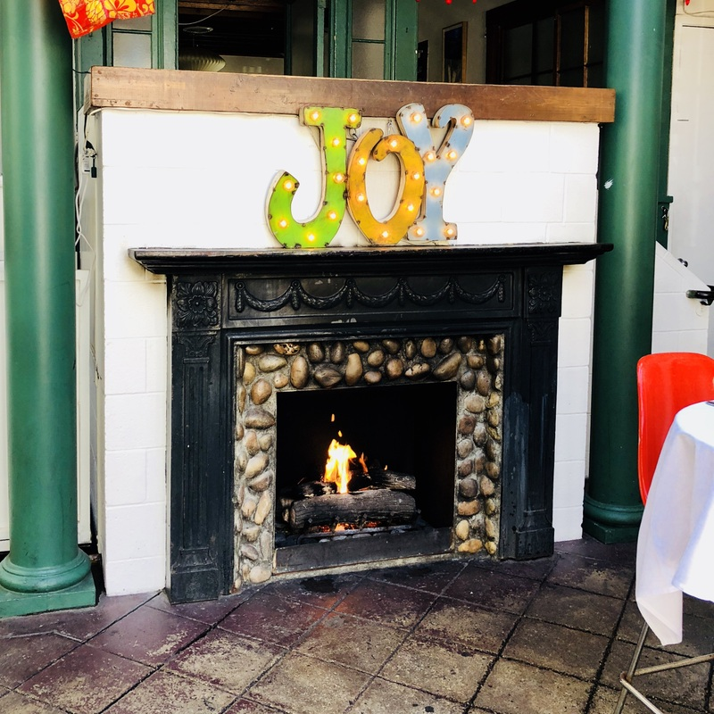 a lit  fireplace at James Beach with a sign that says  the word JOY above it