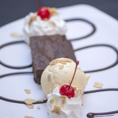 Cream, ice cream and brownie dessert with cherries