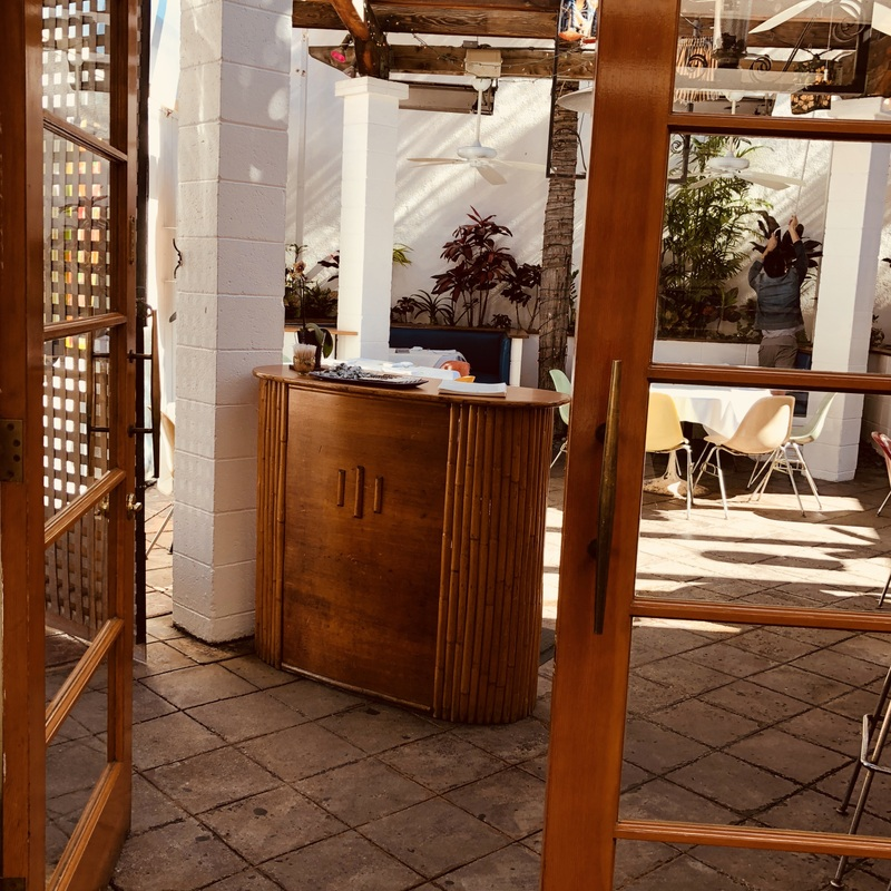 a bamboo bar host stand at the entrance