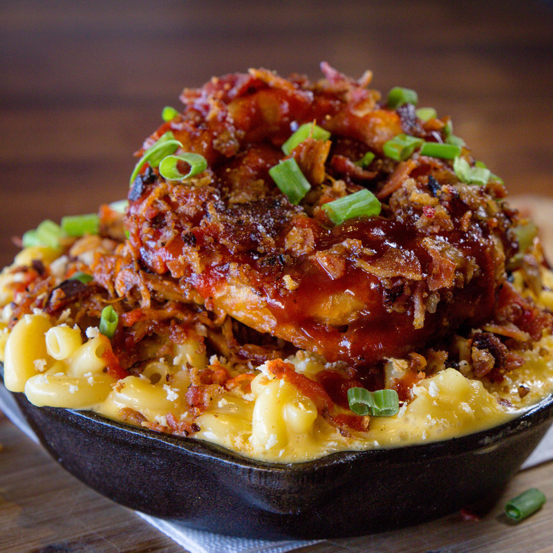 The Elvis: The Norm Mac topped with crispy bacon, bourbon bbq pulled pork, crispy onion ring, sriracha sauce