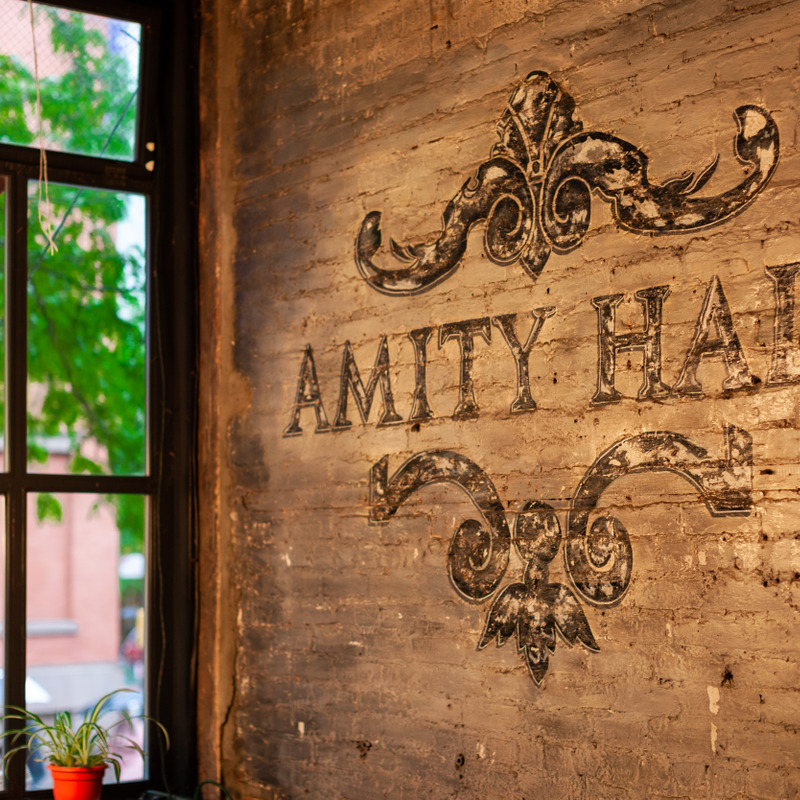 The Amity Hall Logo painted on one of our brick walls