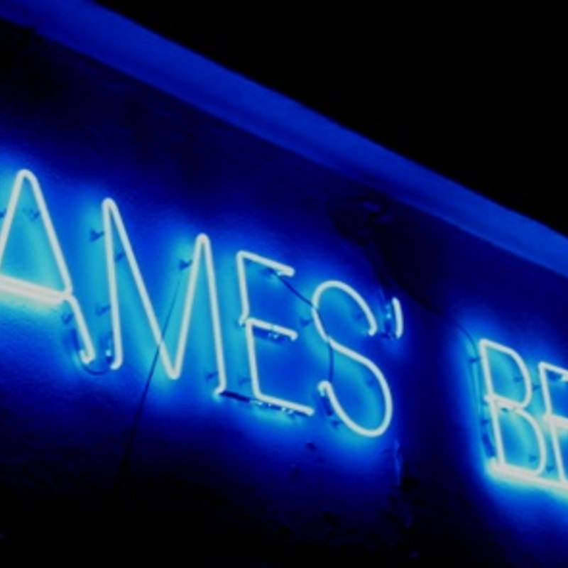 The blue James beach neon sign at night
