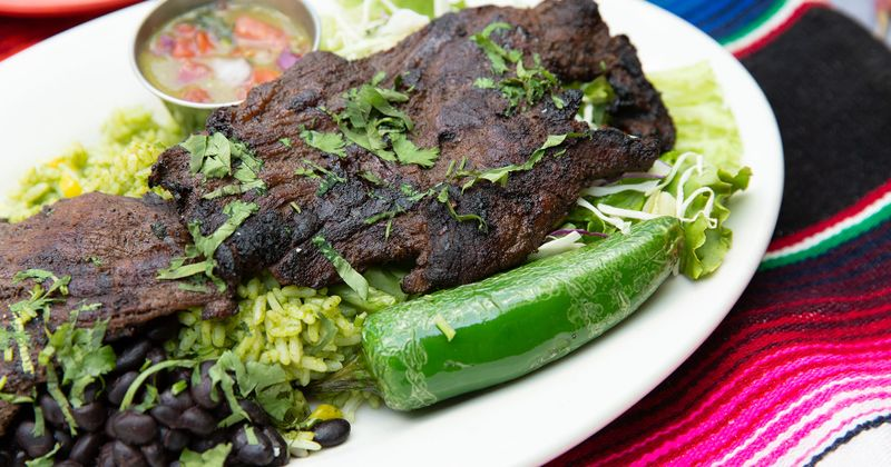 Grilled flank skirt steak served with green rice, black beans, pico de gallo