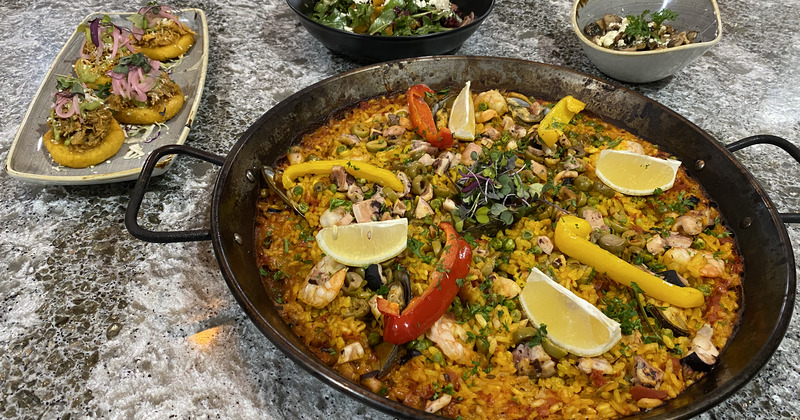 shrimp paella with fresh papers and lemons on top