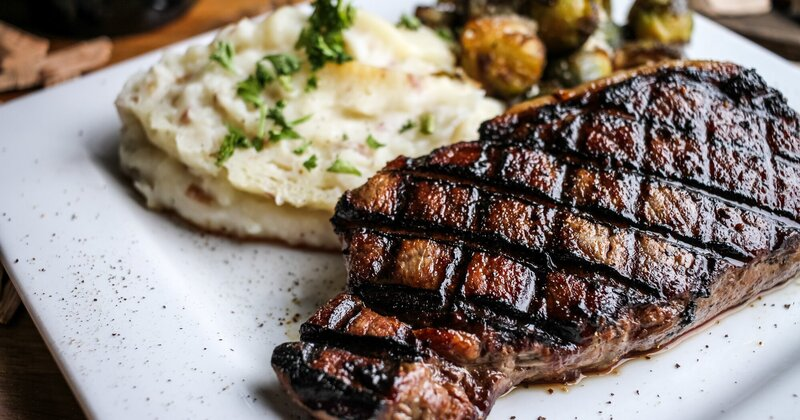 Ribeye served with mashed potatoes and fried Brussels sprouts