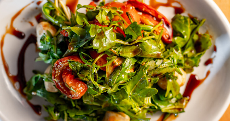 Salad with nuts, arugula, dried tomatoes and soy sauce