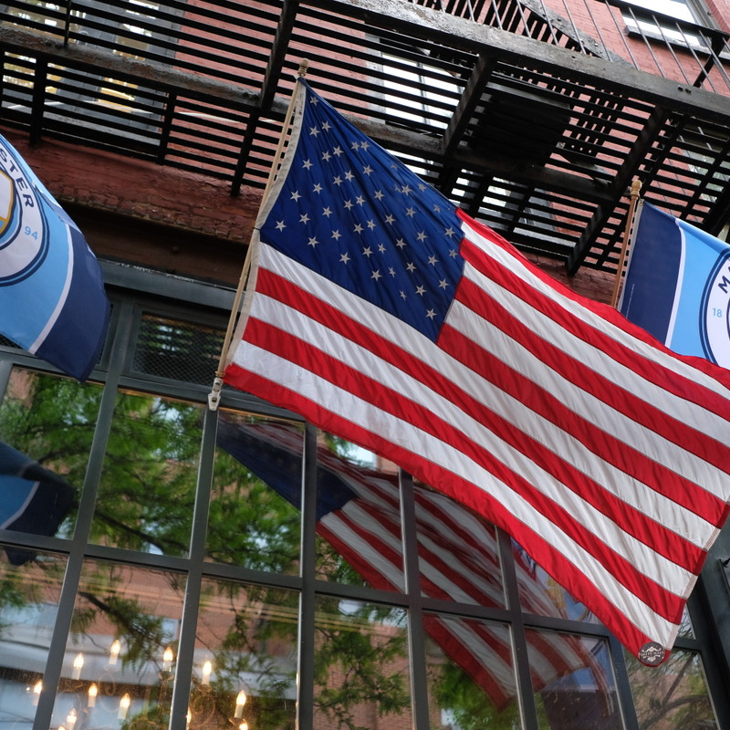 Amity Store front with USA Flag and Manchester City Flags