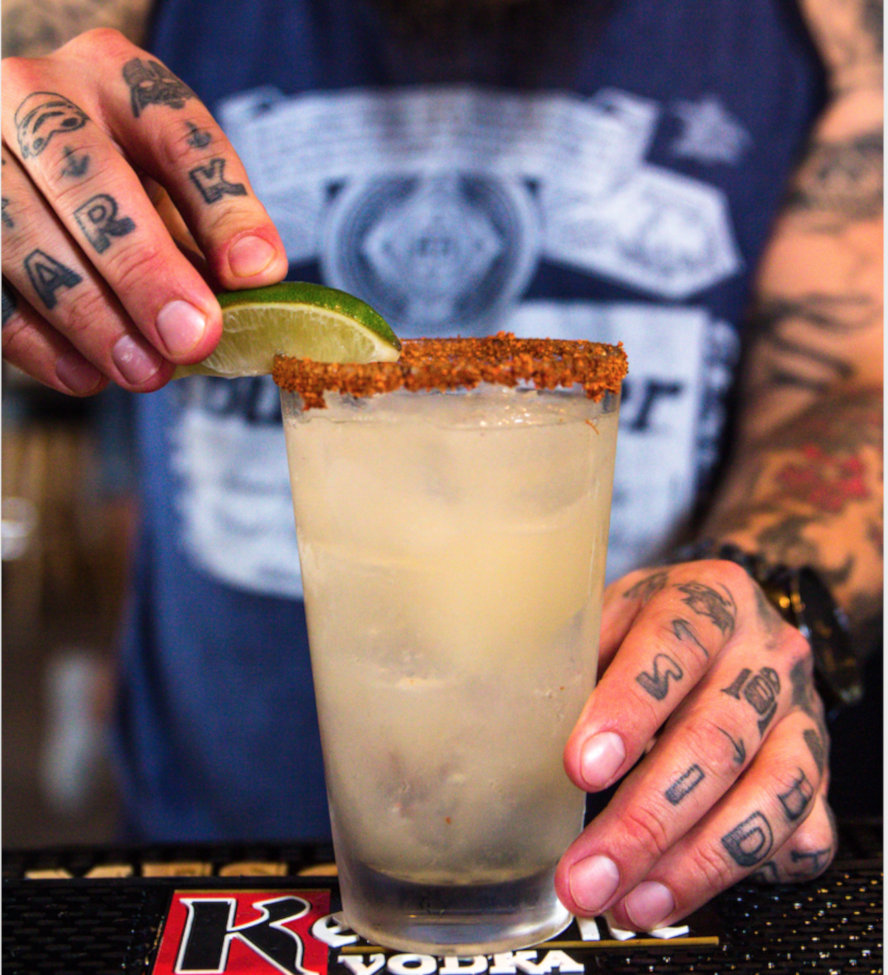Staff member making a cocktail with lime and ice