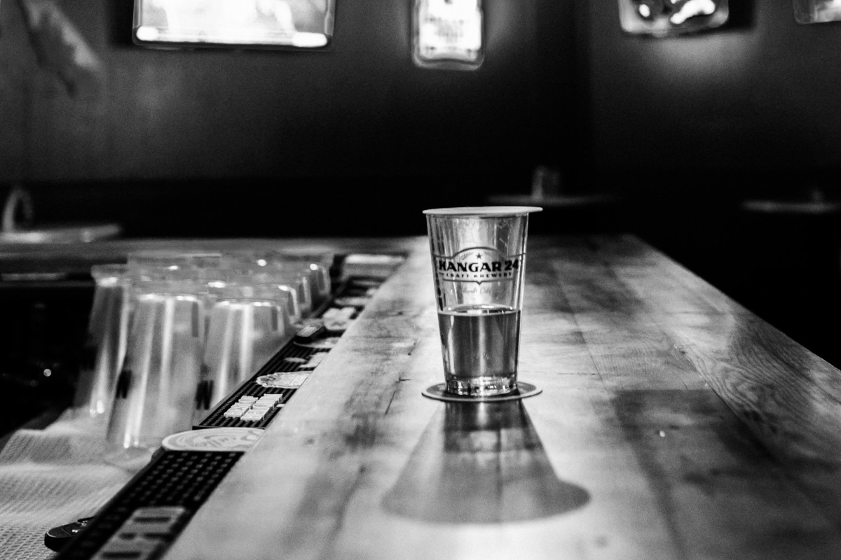 A shot glass on the bar, black and white