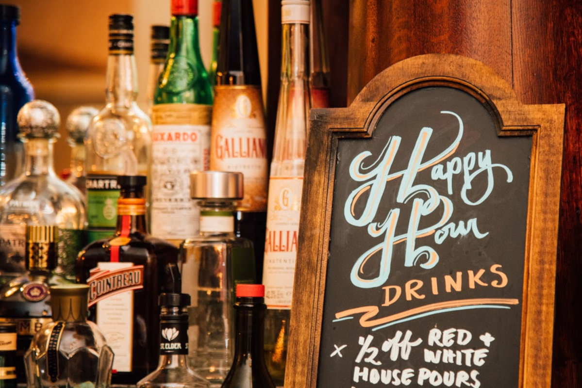 Happy hour board and various liquor bottles