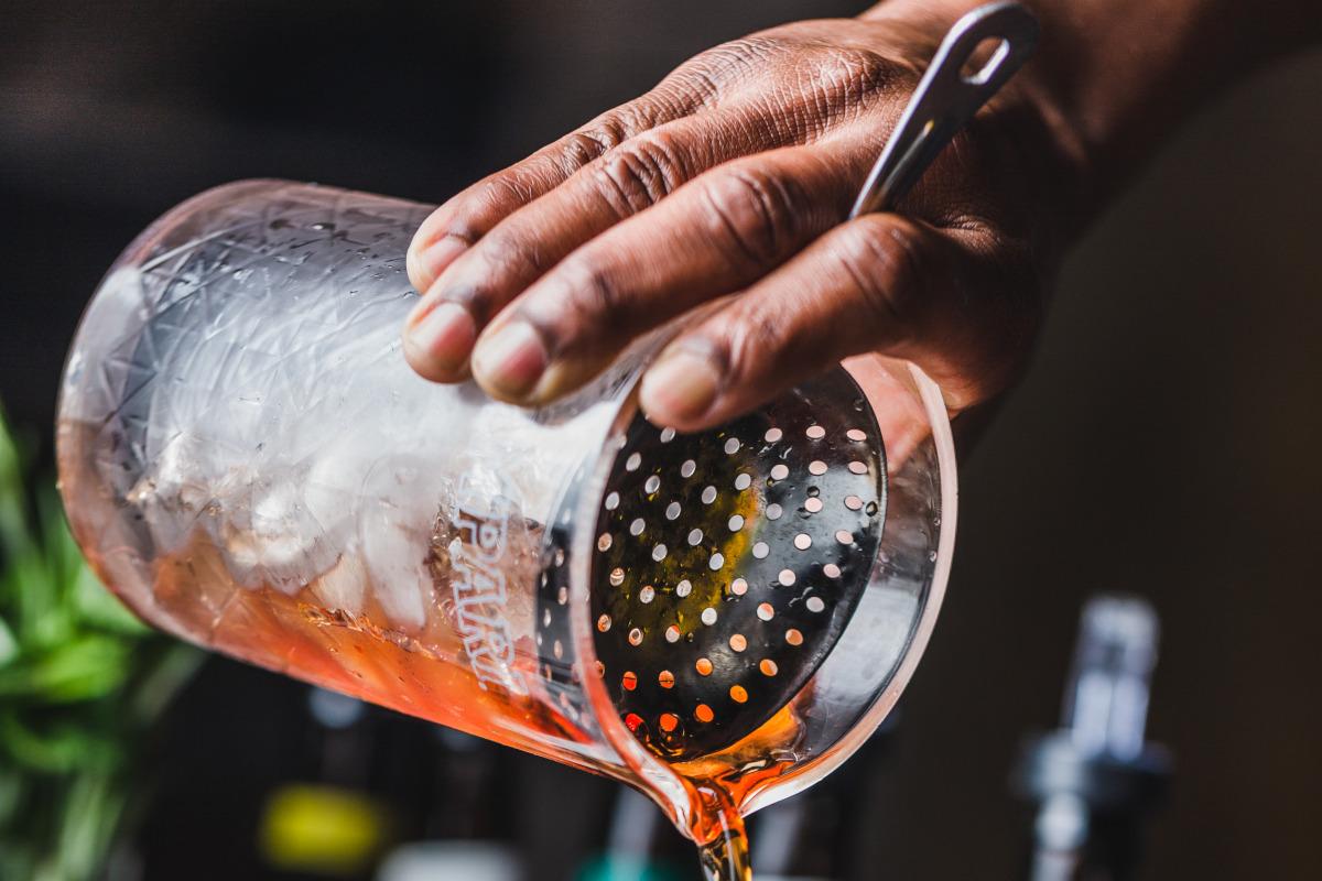 Staff member making Manhattan cocktail