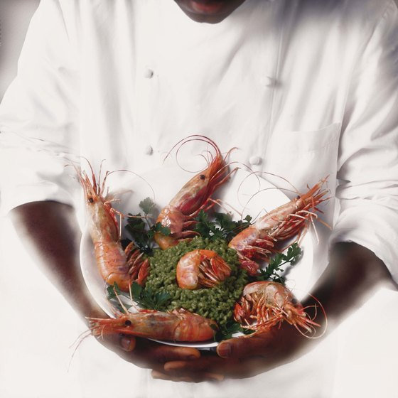 a chef holding a bowl with crawfish and salad