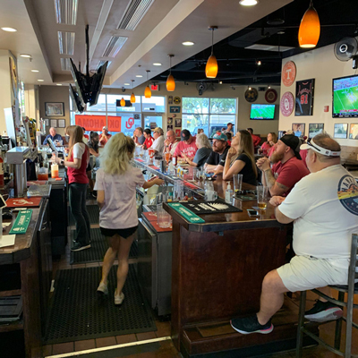 Interior, guests sitting at the bar, watching a game