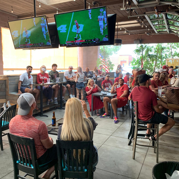 Guests enjoying drinks, watching a game