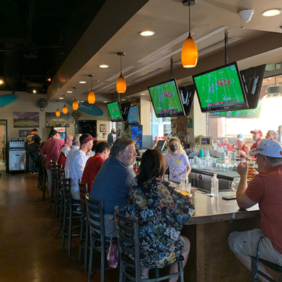 Guests at at he bar, enjoying drinks, watching a game