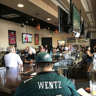 A person in a Wentz jersey and a cap, crowd in the background