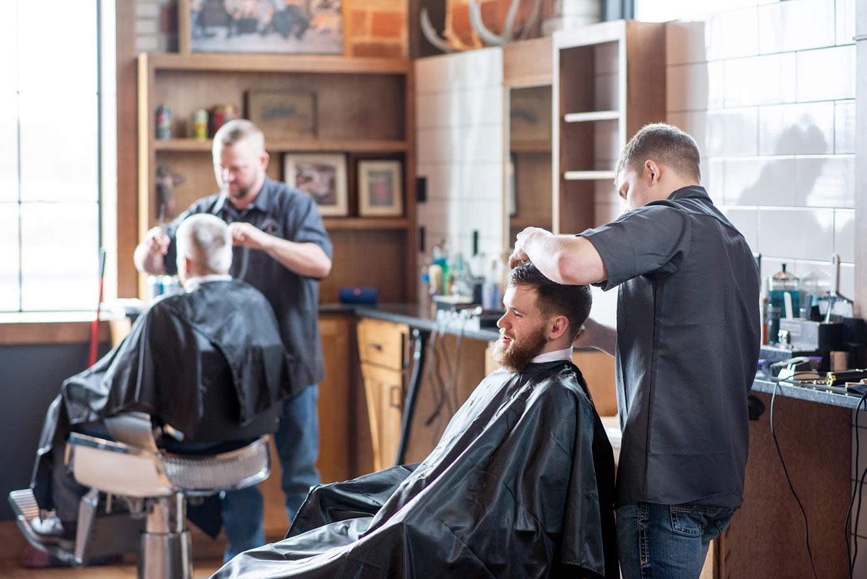 Two barbers cutting hair