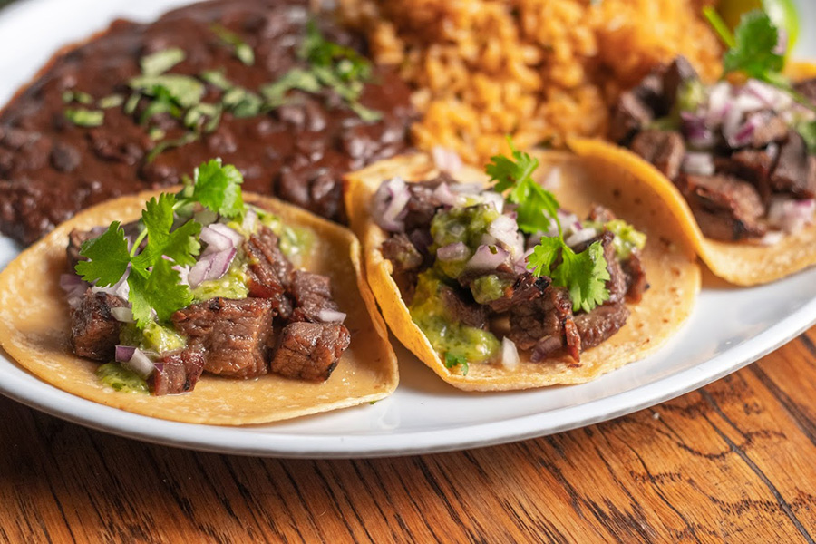 a plate with steak tacos on the table