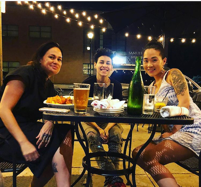 three women smiling at a dinner table