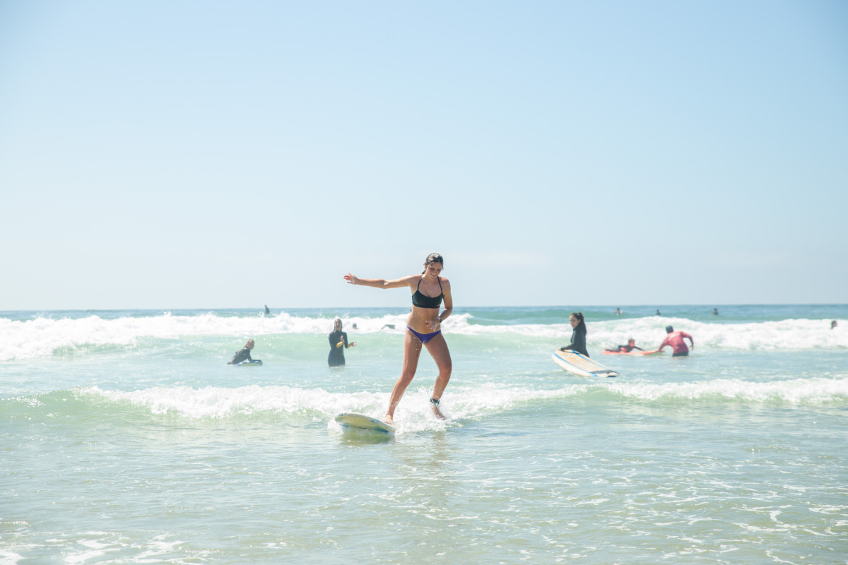 A girl jumping off of a surfing board