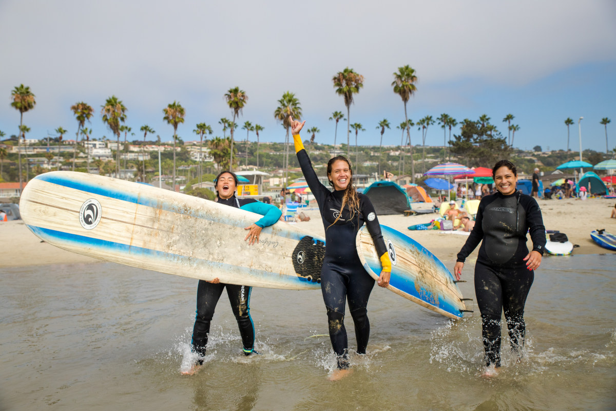 Three smiling girls with surf boards