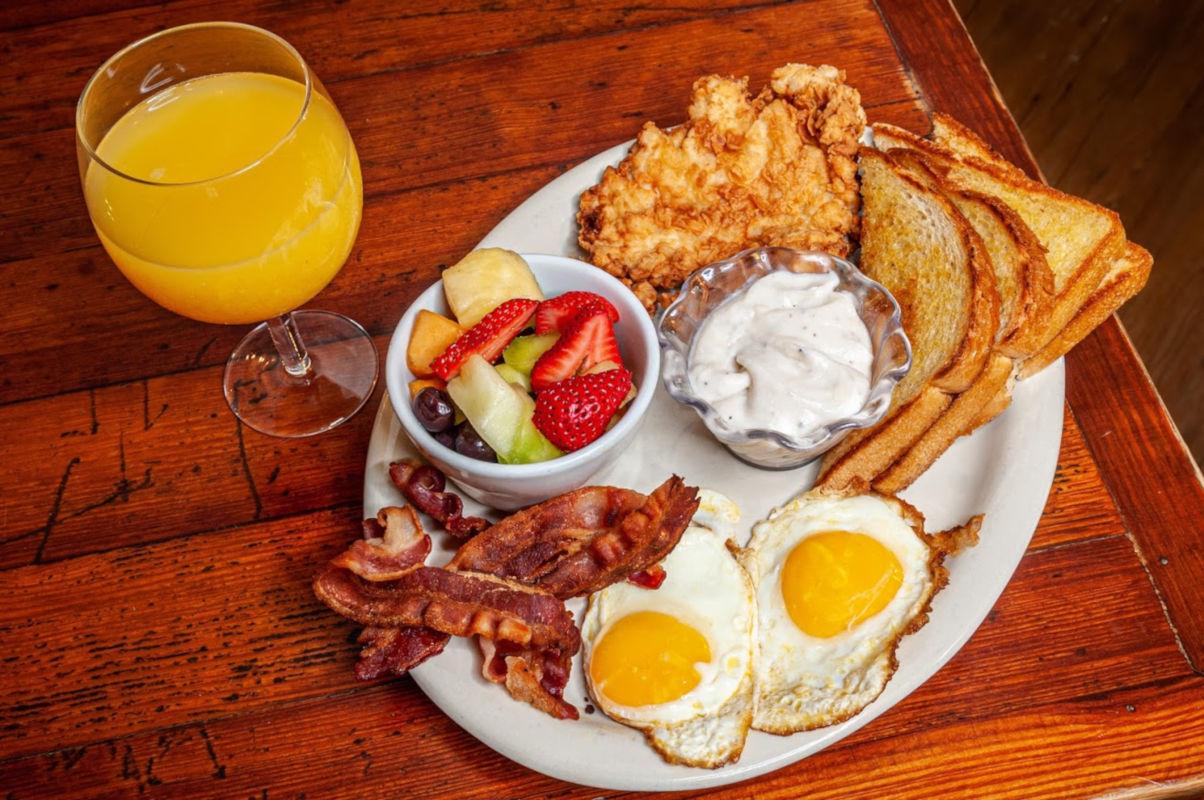 Fried eggs, bacon, dip, bread, fruit salad, orange juice on the side