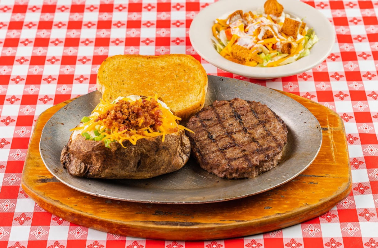 Grilled meat, baked potato and toasted bread