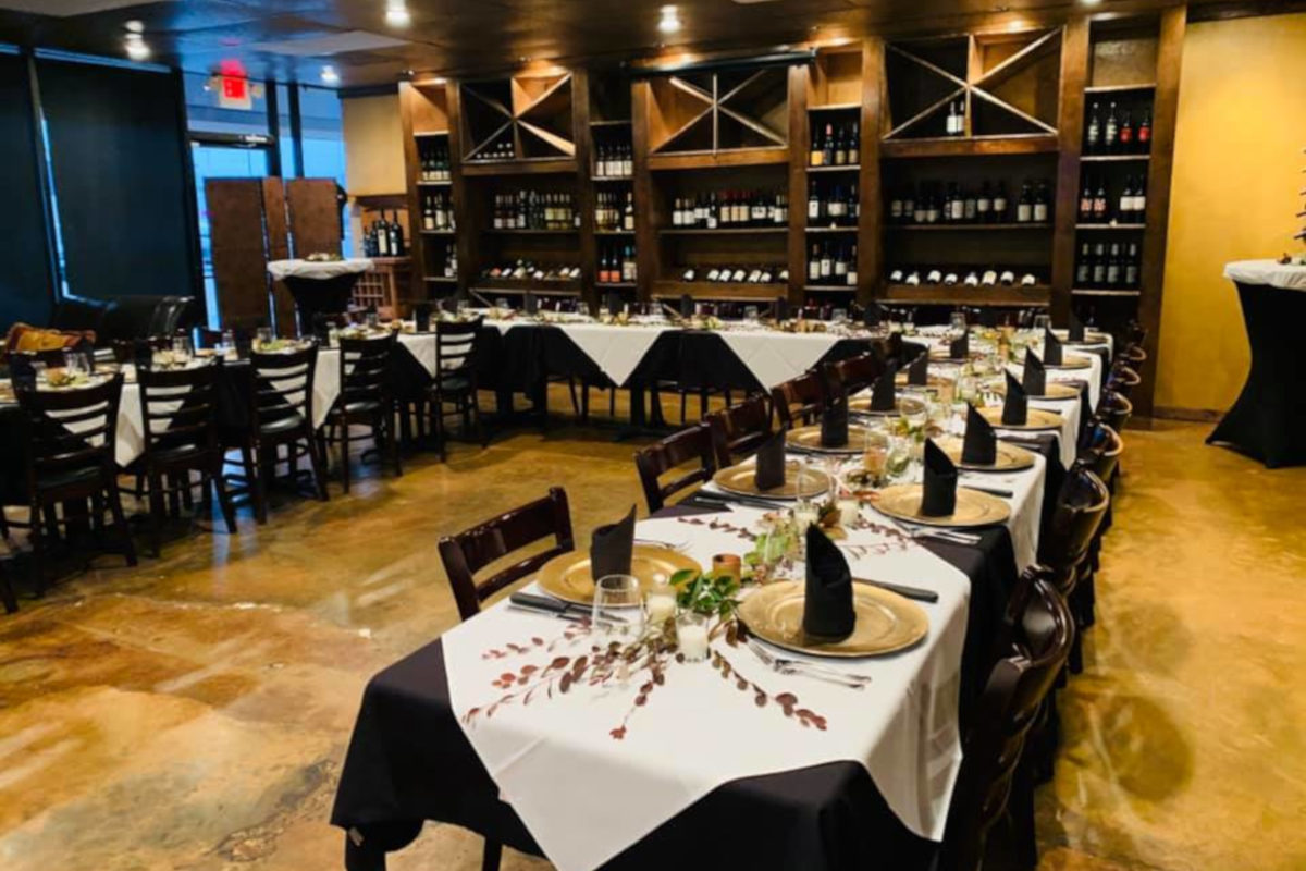 private party area, black napkins, yellow plates, white table cloths