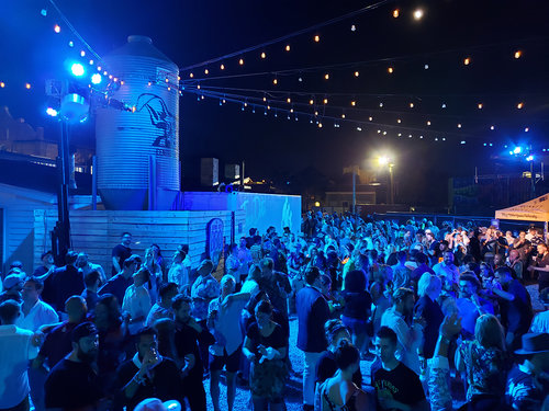 Guests enjoying music and drinks, exterior at night