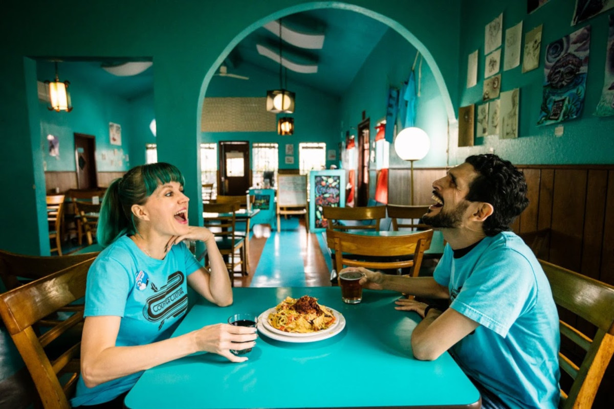 Interior, a couple eating nachos and laughing