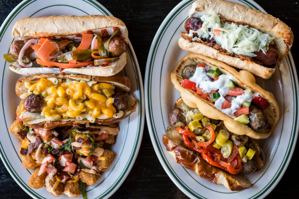 Four different types of sausage sandwiches, salad and fries on the side