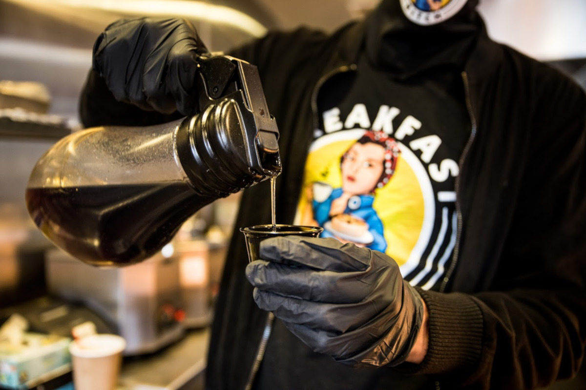 Staff member pouring a coffee in gloves