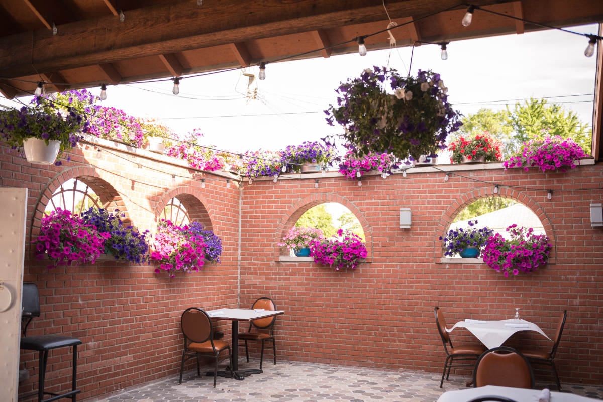 Restaurant exterior, tables for two, flowers decorations on the wall
