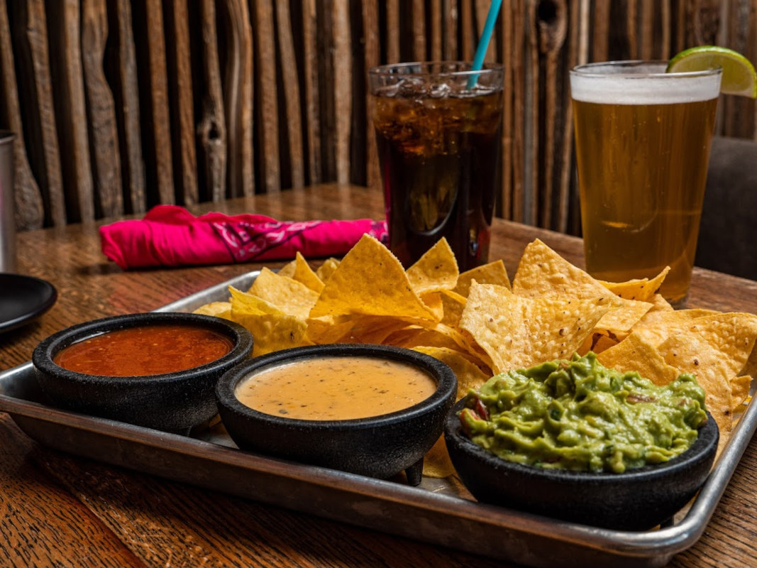 Small guac, queso, and house salsa, with a basket of chips